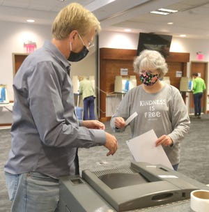 Hudson Library poll worker Eric Blemaster, left, helps Betsy Caric cast her ballot at the Hudson Library and Historical Society on Tuesday, May 4. City voters easily approved Issue 1, which renewed a 2.9-mill levy for the library for five more years.