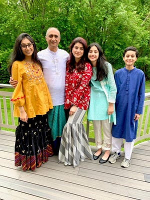 Mona Aslam (middle) stands with her family for holiday photos during last year's Eid al-Fitr. The Cherry Hill family spent the holiday praying at home, eating a home-cooked meal and dropping off gifts around town.