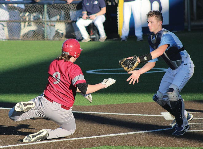 Dewey High's Jared Rodgers, left, goes hard into home plate to try to avoid a tag during baseball action early this season.