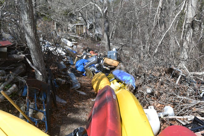 A long path of old watercraft lead to the underground home at 32 Mill Hill Road, where trash fills the property right to the road's edge. The trash has drawn the attention of the Chatham Board of Health, which is pressing the property owner to clean it up.