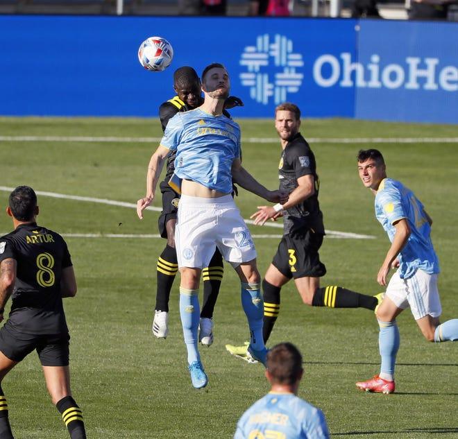 Crew defender Jonathan Mensah goes up for a header against Philadelphia Union forward Kacper Przybylko on April 18.