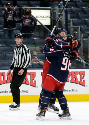 Columbus Blue Jackets center Emil Bemstrom (52) jumps into the arms of Columbus Blue Jackets center Jack Roslovic (96) after scoring his third goal of the game for a hat trick against the Nashville Predators during the third period of Monday's NHL game at Nationwide Arena in Columbus, Ohio, on May 3, 2021.