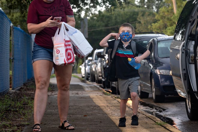 A boy puts on his backpack as he walks into the first day of school at Eustis Elementary School. [Cindy Peterson/Correspondent]