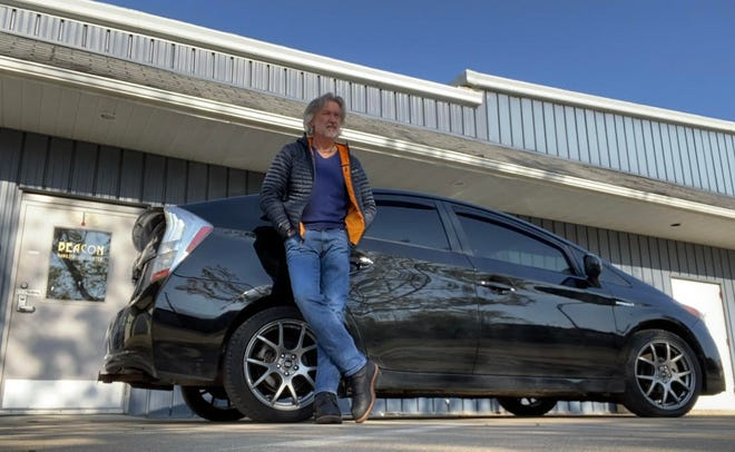Bert MacQueen of Loudonville poses with his Toyota Prius in front of the Beacon Habilitation business he founded a decade ago. MacQueen said he has sold Beacon and will start a website for Prius owners on traveling and solo camping in the vehicle.