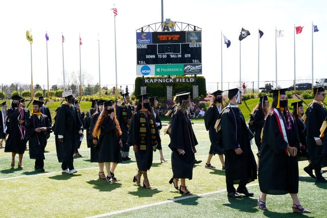 Adrian College graduates enter the Adrian College football field at Docking Stadium during Sunday's commencement exercises, which were held for the December 2020 graduates and the spring 2021 grads. Sunday's graduation was the second day-in-a-row in which the college hosted commencement on campus. Saturday's graduation was for the class of 2020.