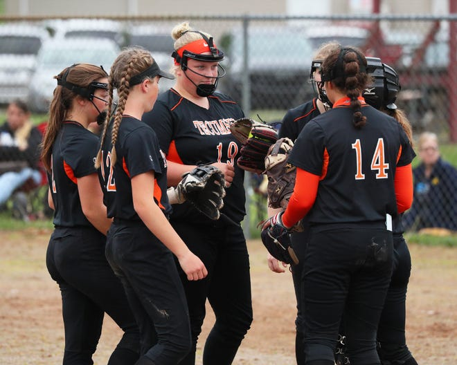 Tecumseh softball infields meets in the pitcher's circle during Monday's doubleheader against Adrian.