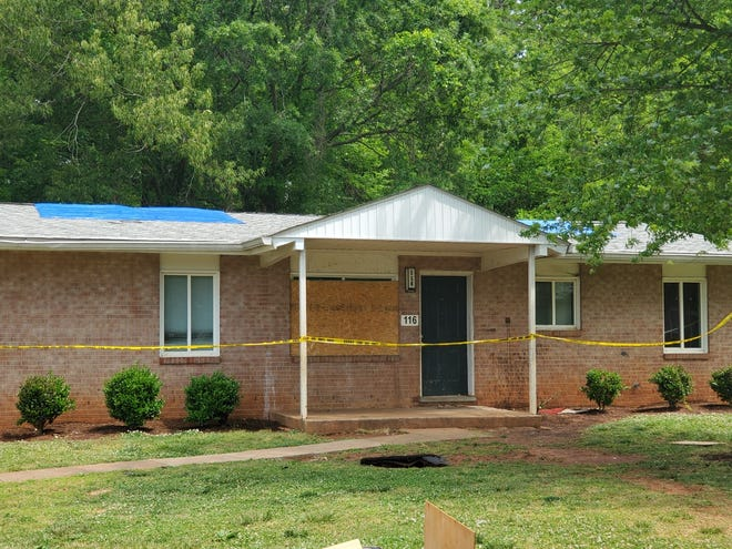 Tarps are visible on the roof and caution tape surrounds a home on Hankins Drive in Lexington where a fire occurred Saturday.