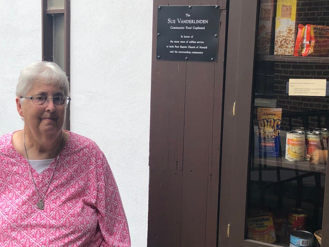Sue Vanderlinden stands by the First Baptist Church of Hornell food cupboard that bears her name.