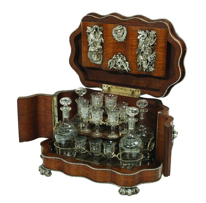 """This oak 19th-century """"cave a liqueur"""" holds four decanters and 16 liqueur glasses. It is decorated with silvered mounts of hunting dogs. The 11-inch-high box sold at New Orleans Auction Galleries for $4,250."""