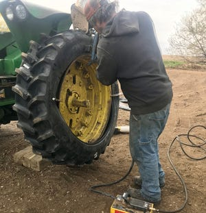 """While using a tire iron, this man was dubbed the """"Tire Guy"""" by columnist Jerry Nelson."""