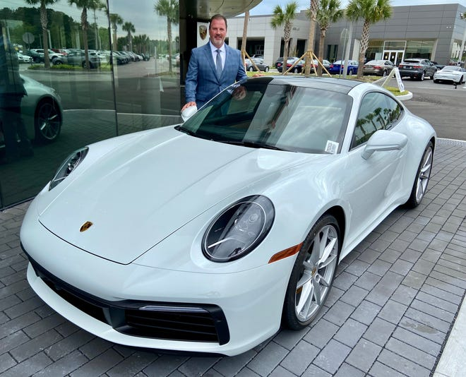Garry Redig, vice president for Fields Auto Group and this year's JADA president and auto show chairman, stands behind a sleek 2021 911 Carrera sports car at his new 42,000-square-foot Porsche Jacksonville dealership on Atlantic Boulevard.