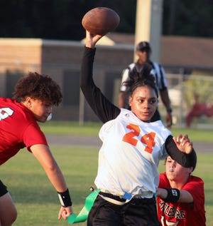 Tallahassee FAMU's Erica Turral (24) attempts to escape the flag pulls of Middleburg's Cheyenne Jenkins (9) and Laura Palagyi (17) during an FHSAA flag football regional final on May 3, 2021. [Clayton Freeman/Florida Times-Union]