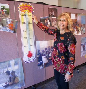 Karen Doy, chairman of the Missions Committee at Grace United Methodist Church in Geneseo, is shown by the gauge used to measure the progress of meeting the goal of $25,000 for the community of Augustin, Haiti