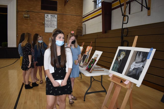 Students look at art displays during MusArt on Wednesday, April 28, at Cambridge High School.