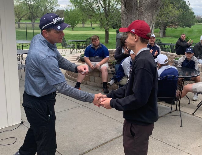 Plainville's Parker Krob, right, shakes hands with TMP golf coach Bryan VonFeldt after Krob won the TMP Invitational on Monday at Smoky Hill Country Club.