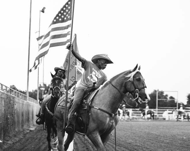 Robert Criff of Kansas City is holding the American flag during a rodeo in Oklahoma.