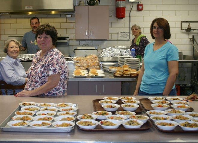 Pictured in the foreground from left in the kitchen at Bethany United Church of Christ are: Mary Joe Trail, Cindy Kahn, and Tammy Jensen. In the back row from left are  Andy McVan and Rebecca Wachover. This photo was taken before the COVID-19 pandemic. The church is marking its 30th anniversary of offering a free monthly meal.