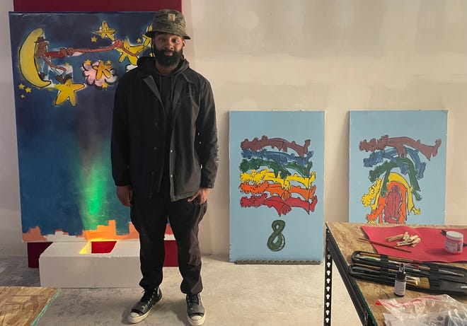 Brother Maars stands in front of his paintings for the Three Twenty Gallery in Las Animas. The art will be up for sale through an auction.