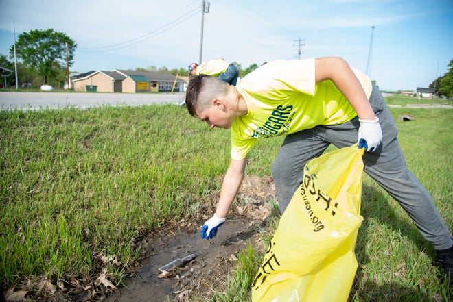 Climax Springs freshman Kaiden Phillips reaches down to pick a glass bottle out of the mud along MO-7.