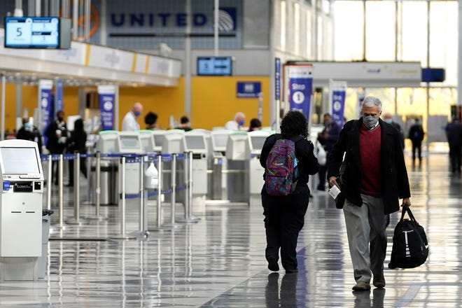 Travelers walk through Terminal 1 at O'Hare International Airport in Chicago on Oct. 14, 2020. [AP File Photo/Nam Y. Huh]