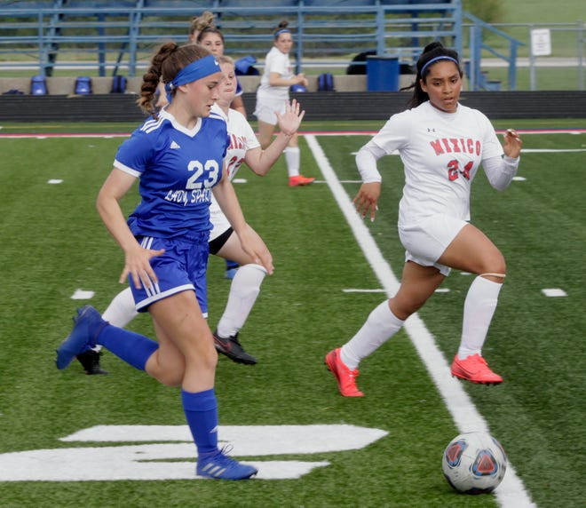 Moberly freshman Addie Holloway (#23) toes the soccer ball up the field Monday at Dr. Larry K. Noel Spartan Stadium while Mexico's Estrella Lopez (#24) runs alongside her. The Lady Spartans lost its home conference game 1-0 to Mexico.