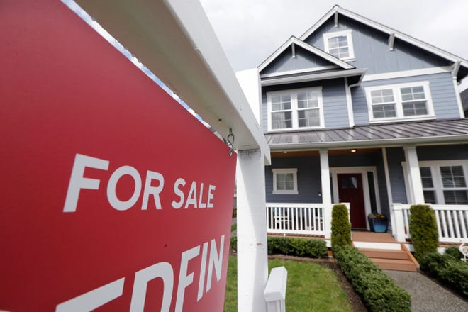 """A """"For Sale"""" sign stands in front of a home that is in the process of being sold in Monroe, Washington. [AP File Photo/Elaine Thompson]"""