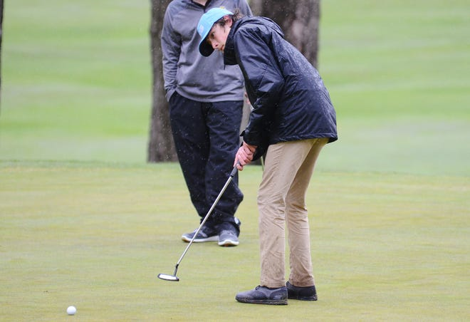 Petoskey golfer Max Faulkner watches his putt as the rain pours down around him at the Petoskey-Bay View Country Club on Monday.
