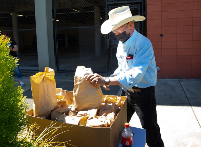 Thomas Green hands out snacks for people attending the Eugene Community Court, which is being held at the Eugene municipal court.