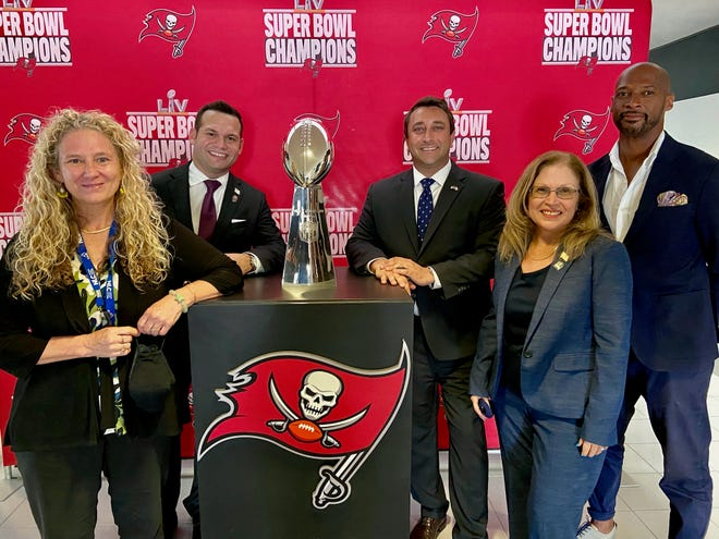 Sarasota City commissioners Jen Ahearn-Koch, Erik Arroyo, Hagen Brody, Liz Alpert and Kyle Battie pose with Vince Lombardi Trophy on Monday. The Tampa Bay Buccaneers were honored at Sarasota City Hall for their historic Super Bowl victory in February.