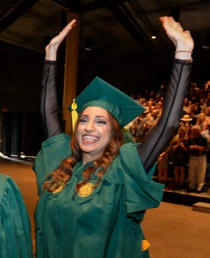 USF Sarasota-Manatee graduate Sondos Dartawil waves to her family during the 2019 commencement ceremony at the Bradenton Area Convention Center. USF is planning an in-person graduation ceremony for Saturday in St. Petersburg that will include students from the local campus as well as the Tampa and St. Pete campuses.