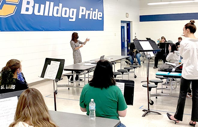 Bethany Stanton leads the Centreville High School band through a rehearsal for a performance at the courthouse lawn.