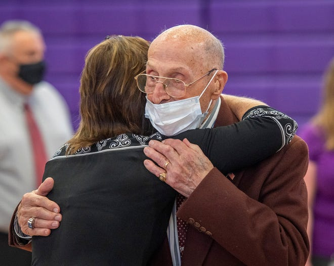 Clarence A. Bachand gets a hug from Sue Foskett during a ceremony to honor his 53 years of service to the Bay Path Regional Vocational Technical High School Tuesday. Foskett is the executive assistant to the superintendent.