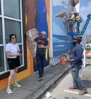 From left, artists Olga Guy, Jayson Kretzer and Christon Anderson discuss the mural wall as Paul Brent works on details of his segment on a boom lift in the background.