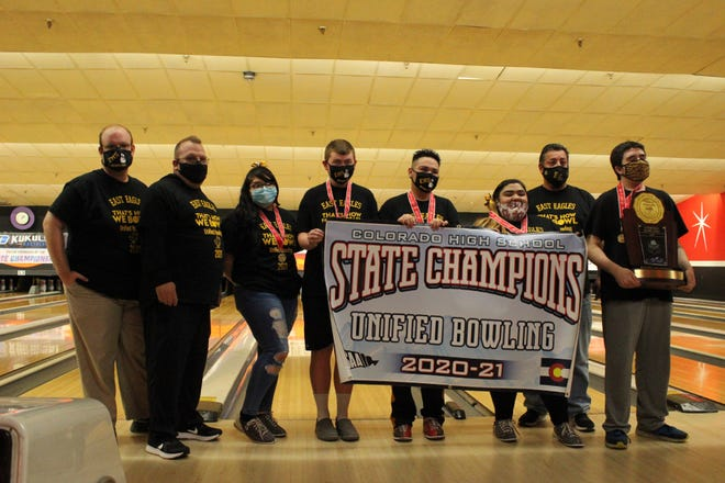 Pueblo East unified bowling stands with their trophy and banner after winning the sport's first sanctioned state title.