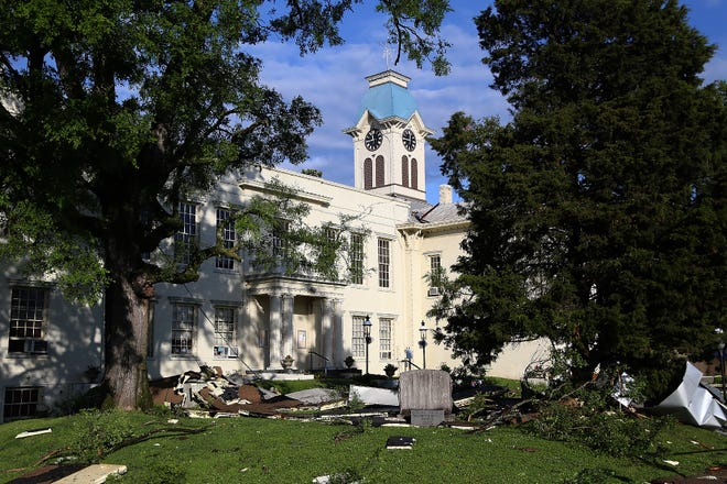 Downed trees and roof panels litter the Crawford County Courthouse lawn, Tuesday, May 4, after a fast-moving storm passed through the area overnight.
