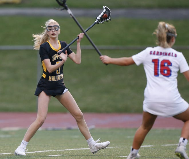 Upper Arlington's Rian Adkins works against Thomas Worthington's Tate Beegle earlier this season. Adkins started the season on defense but moved to offense because of injuries to teammates. She had 31 goals as the Golden Bears were 16-0 before playing Dublin Jerome on May 7.