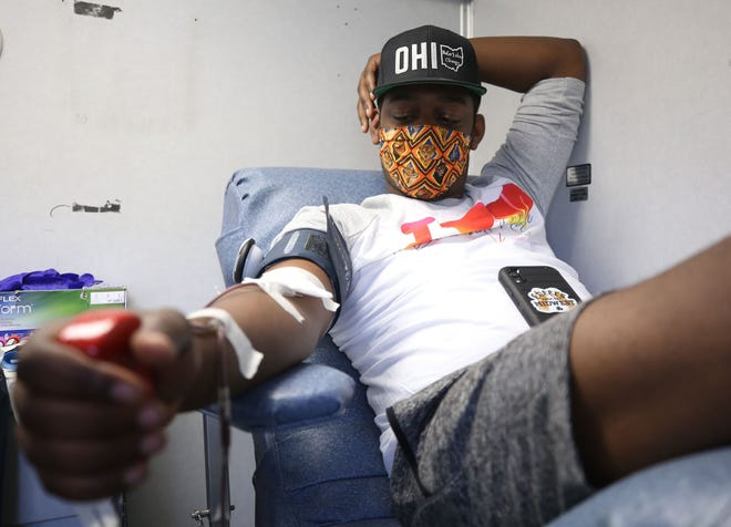 """Anthony """"Sizzle"""" Perry Jr., co-owner and founder of Crafted Culture Brewing Co., donates blood during the Pint for a Pint blood drive at the brewery, 505 Morrison Road in Gahanna, on May 3."""