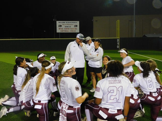 The Red Oak Lady Hawks listen as their head coach gives a victory speech to his excited team that moves on in the playoffs.