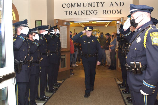 Watertown Police Lt. Chrisopher Munger salutes the Watertown Police Honor Guard during his retirement ceremony.