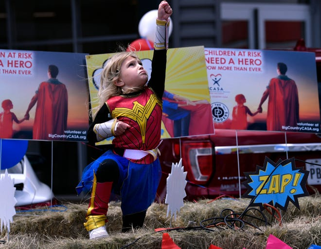 Esther McQueen, 5, dances to superhero movie soundtracks played beside a trailer at Arrow Ford on Tuesday. Big Country CASA, an organization that works with abused and neglected children in foster care, was holding the fundraiser in conjunction with Abilene Gives.