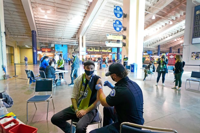 In this May 2, 2021, photo, Austin Kennedy, left, a Seattle Sounders season ticket holder, gets the Johnson & Johnson COVID-19 vaccine at a clinic in a concourse at Lumen Field in Seattle, prior to an MLS soccer match between the Sounders and the Los Angeles Galaxy. Rising coronavirus cases and hospitalizations in Washington and Oregon have led Oregon officials to move toward further restrictions. Washington is taking a two-week pause to evaluate before making a decision.  (AP Photo/Ted S. Warren, File)