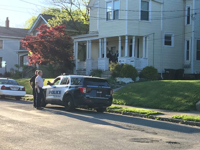 Investigators are on the porch of a residence Friday on Tilden Avenue in Norwood where a man who police said refused to come out in the afternoon was found dead inside hours later by SWAT team officers.