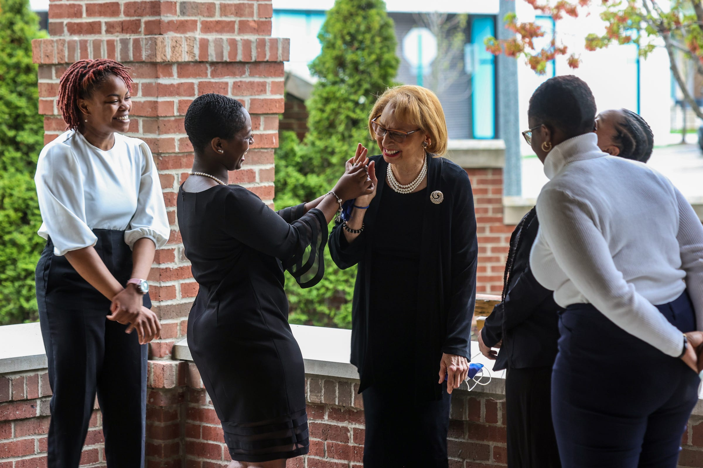 Wayne State University Student Arnell Kinney, 21, of Detroit looks on as Nia Anderson, 23, of Detroit helps President Jennifer Poole, 75, of West Bloomfield with her lipstick with help from Dominique Jenkins, 28, of Detroit and Sydni Alexis Elebra, 20, of Detroit at the Village of Brush Park Manor Paradise Valley in Detroit on April 29, 2021. Poole is presenting the students with the Jessie P. Slaton Scholarship awarded by the Elliottorian Business and Professional Woman's Club. The Elliottorian Business and Professional Women's Club is the first club of Black business women in Detroit and Michigan and was founded in 1928.