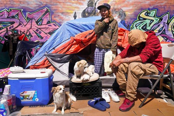 Lucio Lopez, kiri, berbicara dengan teman-teman saat dia berdiri di tenda yang merupakan bagian dari perkemahan tunawisma di wilayah Queens di New York, Selasa, 13 April 2021.