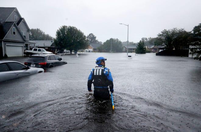 Pada hari Minggu ini, 16 September 2018 file foto, seorang anggota tim pencarian dan penyelamatan perkotaan Satgas Carolina Utara mengarungi lingkungan yang banjir mencari penduduk yang tetap tinggal saat Florence membuang hujan lebat di Fayetteville, NC