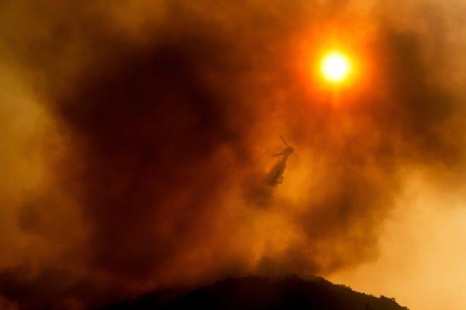Dalam file foto Senin 17 Agustus 2020 ini, sebuah helikopter menjatuhkan air saat memerangi Kebakaran Sungai di Salinas, California. Petugas pemadam kebakaran di seluruh wilayah bergegas untuk menahan lusinan api yang dipicu oleh sambaran petir selama gelombang panas di seluruh negara bagian.