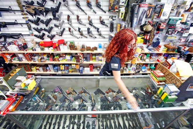 Diane Rowe, pemilik Papas Pawn & Gun, mendisinfeksi konter setelah pelanggan datang melihat senjata di Grants, NM, Senin, 27 April 2020.