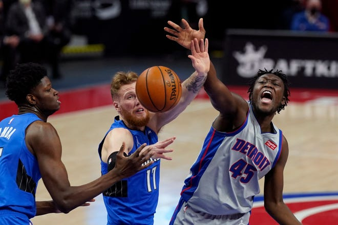 Penyerang Detroit Pistons, Sekou Doumbouya (45) kehilangan penguasaan bola di samping penyerang Orlando Magic James Ennis III (11) dan center Mo Bamba pada paruh pertama pertandingan mereka, Senin, 3 Mei 2021, di Detroit.