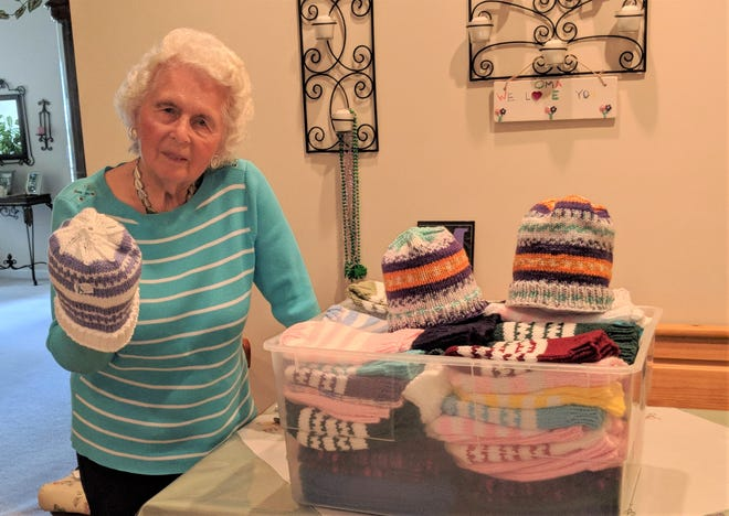 95-year-old Marie Vessels holds a hand-knit hat she made and is getting ready to donate.