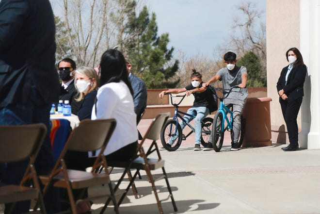 In this Monday, April 5, 2021, photo Jonathan Chilton, 14, center, sits on his BMX bike in front of the New Mexico state capitol ahead of a bill signing by the governor in Santa Fe, N.M.